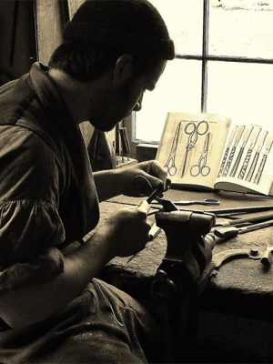 Here the Farmers' Museum's master blacksmith works on a pair of 1840s scissors.