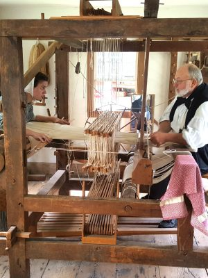 Operating a loom as large as the one shown here takes years of practice.  Here our master interpreter passes along knowledge to another interpreter.