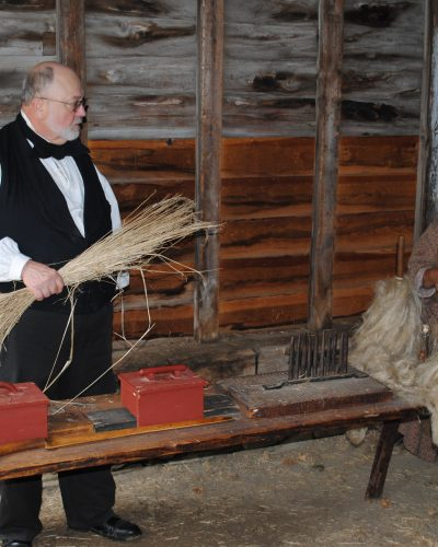 Here one interpreter shows the unworked flax; the next interpreter sits next to budles of processed flax ready for spinning.