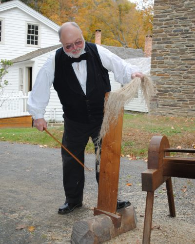 Here a Farmers' Museum Interpreter demonstrates how to use a tool called a brake that helps to separate the fibers from the stalks.