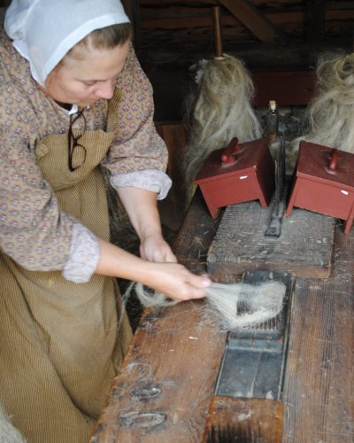 Here the Farmers' Museum interpreter works to pull the flax fibers  repeatedly through a comb of vertical nails called a heckle until they are smooth and polished. At this point they look and feel like horse hair.