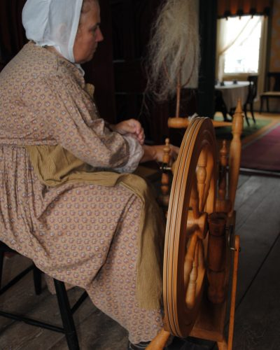 Farmers' Museum Interpreters not only spin sheep wool they also grow, process, and spin flax.