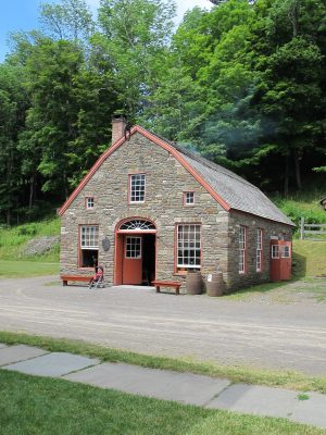 The Peleg Field Blacksmith Shop is a stone building featuring two forges where blacksmiths work daily.